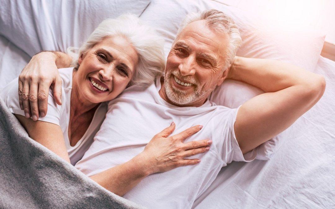 Seniors souriants dans un lit